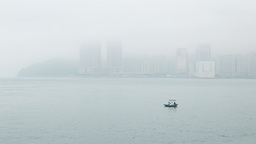 Two fishermen in a tiny boat, against foggy misty land shore Footage
