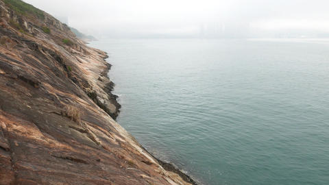 Bottom of cliff and side horizon view of massive rock shore, falling down to sea Footage