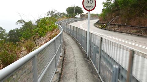 Serpentine road on hillside, traffic sign warns about dangerous turn Footage