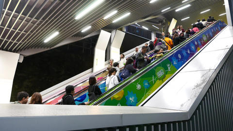 People moving up escalator, illuminated passage, black outside Footage