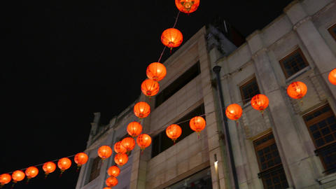Beautiful garland from chinese paper lanterns against night sky and building Live Action