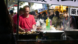Wok with boiling soup on night market stand, street restaurant Live Action
