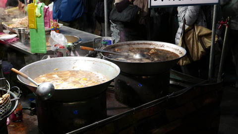 Open kitchen place at night market, close view to wok full of boiling broth Live Action