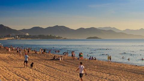 vietnamese people walk on beach swim in sea at dawn Footage