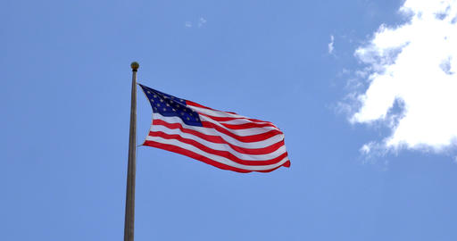 4K American flag - star and stripes floating over a blue sky Footage