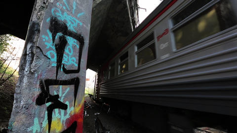 Moving suburban electric train under bridge moves on camera. Graffiti Live Action