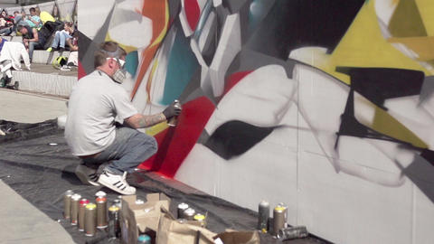 Graffiti artist sitting and paint spraying the wall. Slow motion Footage