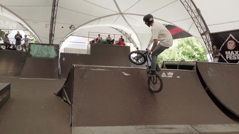 Boy in helmet make tricks on BMX bicycle inside skate park. Audience Slow motion Footage