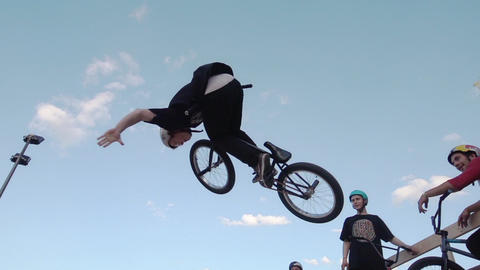 Boy make extreme jump on BMX bicycle in skate park, let go steering wheel in air Footage