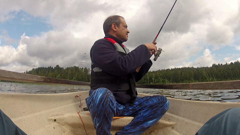 Fisherman catches a fish on rowing boat Stock Video Footage