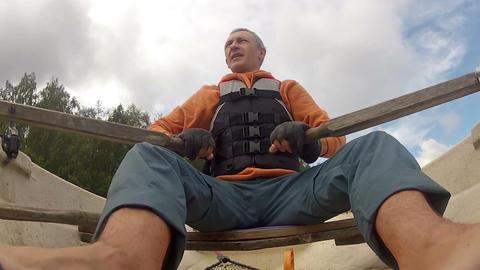 Man in a Life Jacket in a Boat Rowing Oars Stock Video Footage