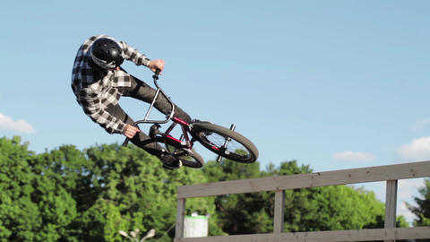 Boy make extreme flips and fall down on BMX bicycle in skate park. Summer Footage