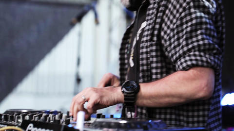 Eldery grandfather DJ at the dj panel on stage. Summer evening Live Action