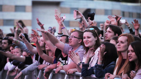Audience watch on stage, raise hands, sing, apploud. Summer live festival Footage