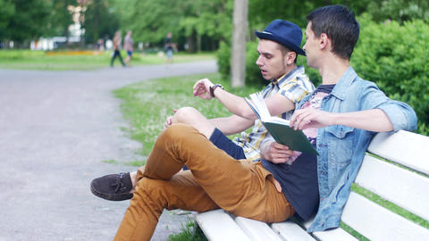 Two boys sit on bench. One read book, ask how much time another boy. Awkwardness Live Action
