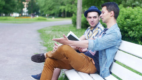 Boy share with friend feeling about read book. Friend look at watch and leave Live Action