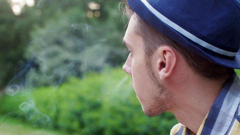 Face of boy in hat smoking cigarette in summer green park. Smoke Footage