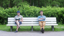 Young boy sit on bench read book, till another boy sit near and say time. Summer Footage