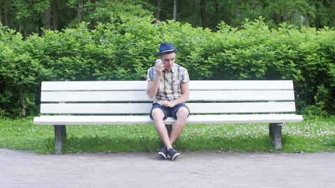 Young boy sit on white bench, waiting, someone call him on phone. Green park Footage