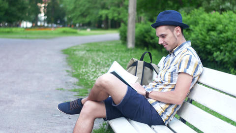 Young boy focused read book on bench of green park, look at watch stand and go Live Action