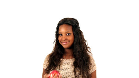 Young African American teenage girl eating an apple, over white background Footage