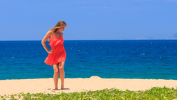 blond girl in red dances barefoot on sand holds hands on hips Footage