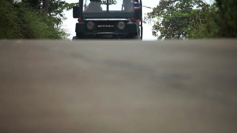 KOH SAMUI, THAILAND - NOVEMBER 9, 2014: Jeep rides on the road in the jungle of Footage