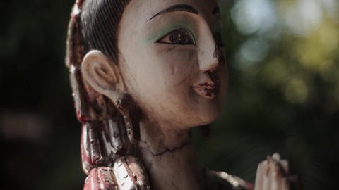 Asian female cracked statuette. Pan vertical. Idol, culture, traditional, rite Footage