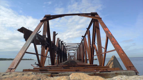 Old huge abandoned railway rusty bridge above water. Coast. Summer. Zoom in Footage
