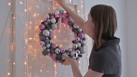 A beautiful woman hanging a Christmas wreath on her home Footage