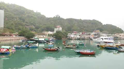 Vivid water and boats in shelter, fishing village on background Footage