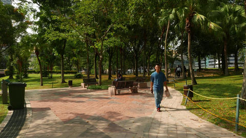 Walkways in KLCC park, rest area bench, security woman, few people Footage