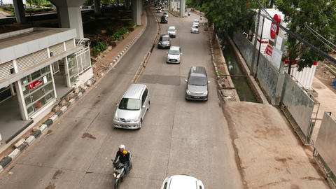 Some traffic, view from above carriageway. Transjakarta bus stop on left Footage