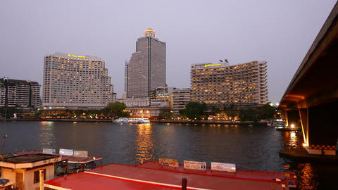 Hotel buildings and tower on riverbank in dusk, sweet hour lighting Footage