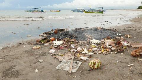 Burning debris and Canang sari remains on Balinese beach, close view ライブ動画