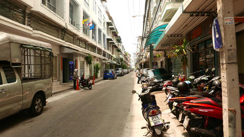 Narrow Charoen Krung alley, tenement-houses facades, vehicles parked, glide shot Footage