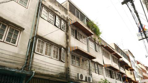 Windows, balcony and facades of Bangkok houses, long slide-pan shot along alley Footage
