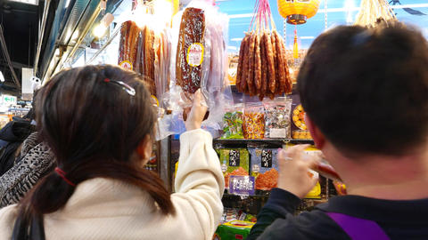 Woman asking seller about ham in plastic, taiwanese indoor bazaar Footage