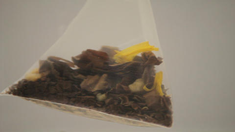 Ungraded: Pyramid Tea Bag Rotates in Water Footage