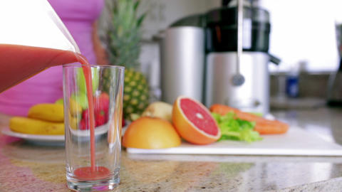 Woman pouring fresh fruit and vegetable juice Footage