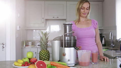 Blonde pouring fresh fruit and vegetable juice Footage