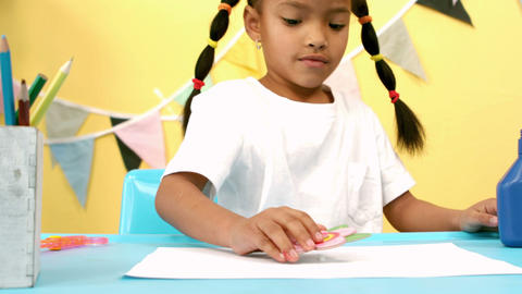 Girl placing flower template on a sheet of paper Footage