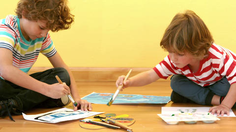 Two small boys painting pictures Footage