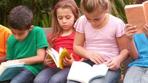 Children reading books at the park Footage