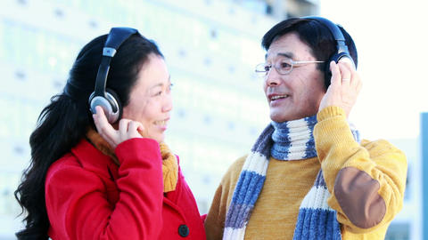 Mature Asian couple listening to music with headphones Footage
