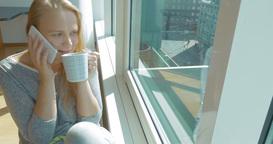 Woman having phone talk and drinking tea Footage