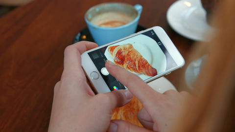 Woman photographing her croissant on smartphone Footage