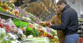 Man and woman buying fresh vegetables in supermarket Footage