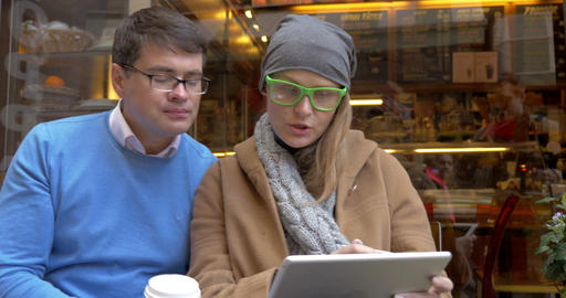 Young couple having coffee and using pad in city Footage