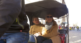 Couple riding in bicycle taxi and talking to each other Footage